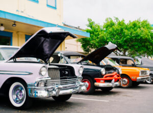 Classic cars with their hoods open line the streets of Old Town for their weekly classic car show.