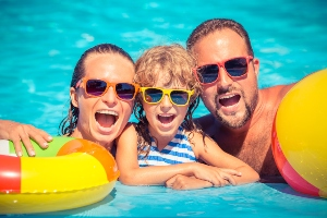 Family enjoying swimming pool and wearing sunglasses