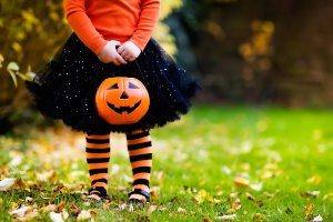 Little girl in halloween costume carrying pumpkin candy basket