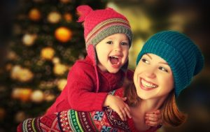Smiling mom poses with laughing baby on back with Christmas trees in background