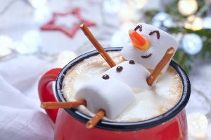 Marshmallow snowman floating in hot chocolate mug